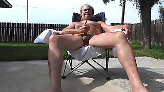 A naked, hairy daddy sunbathing and playing with his penis (masturbating).